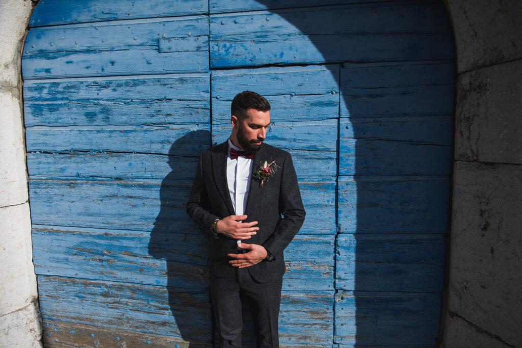 Futur marié devant une porte bleue