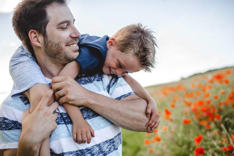 Papa jouant avec son fils devant un champ de coquelicots