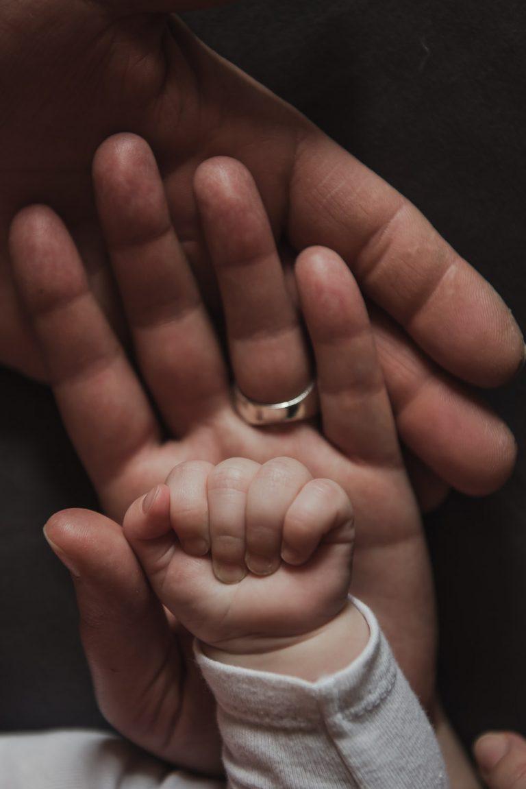 Main de nouveau-né dans les paumes des parents