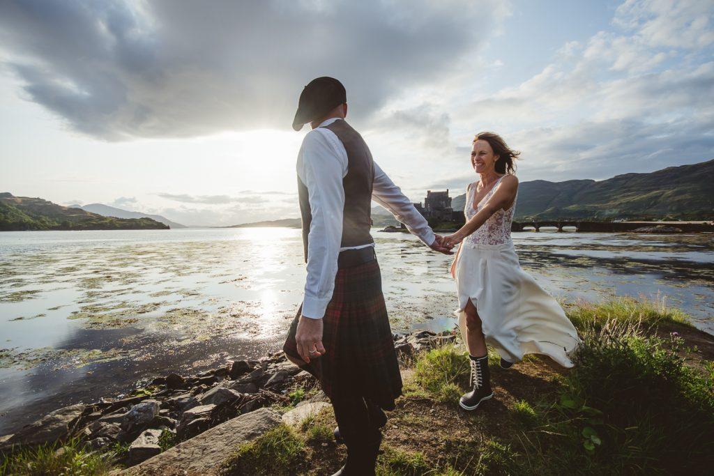Couple main dans la main en tenue de mariage et kilt