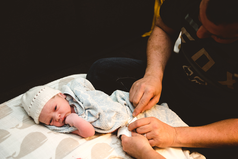 papa coupant le cordon ombilical de son nouveau-né