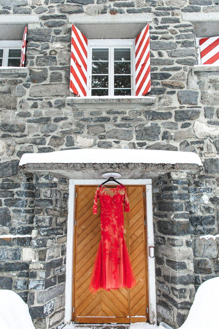 Robe de mariée rouge suspendue à la façade d'un batiment
