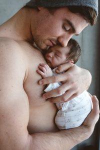 Papa torse nu tenant son nouveau-né dans les bras