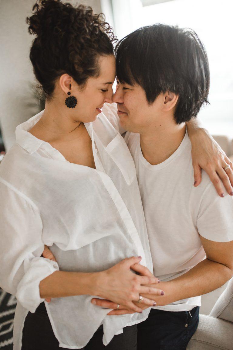 Couple se serrant dans les bras et l'homme touchant le ventre de sa femme
