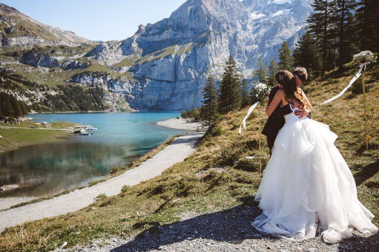 Couple de jeunes mariés s'enlaçant au bord du Lac Oeschinen
