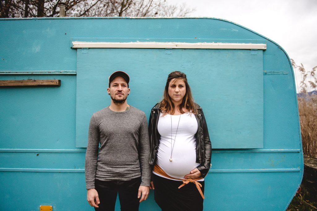 Couple avec une femme enceinte devant une caravane bleue