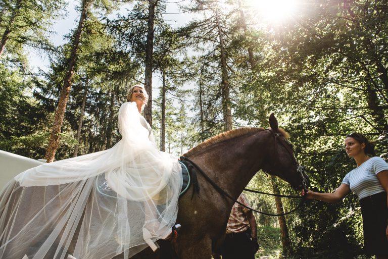 Mariée en robe sur un cheval Valais