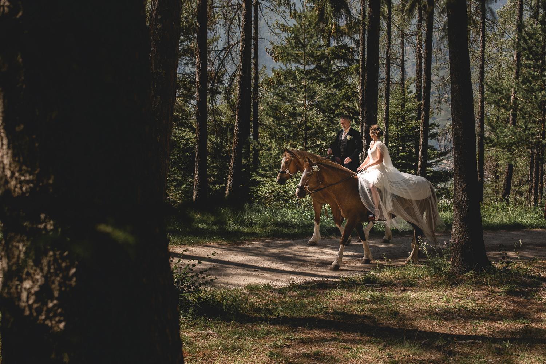Père et fille jeune mariée en robe à cheval dans les bois