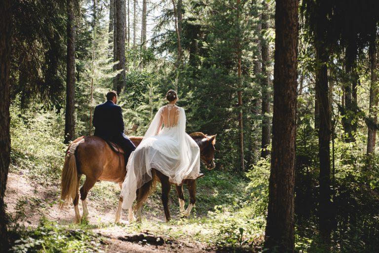 Jeunes maries montant à cheval dans les bois