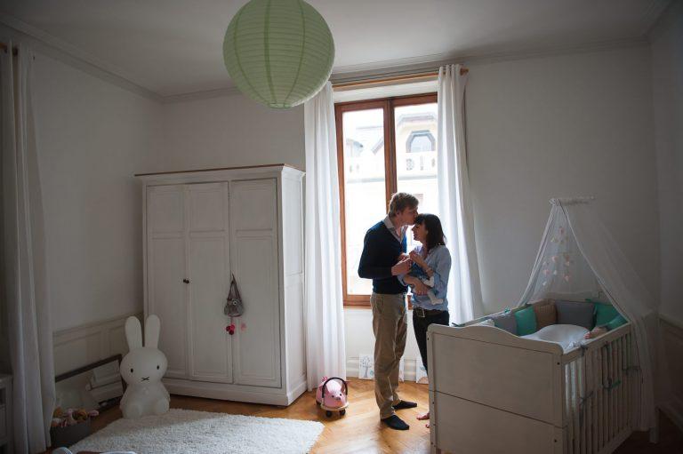 Couple tenant son nouveau-né dans les bras devant une fenêtre