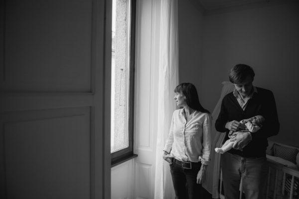 Couple tenant son bébé dans les bras devant une fenêtre noir blanc