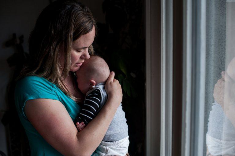 Maman portant son bébé devant la fenêtre trisomie