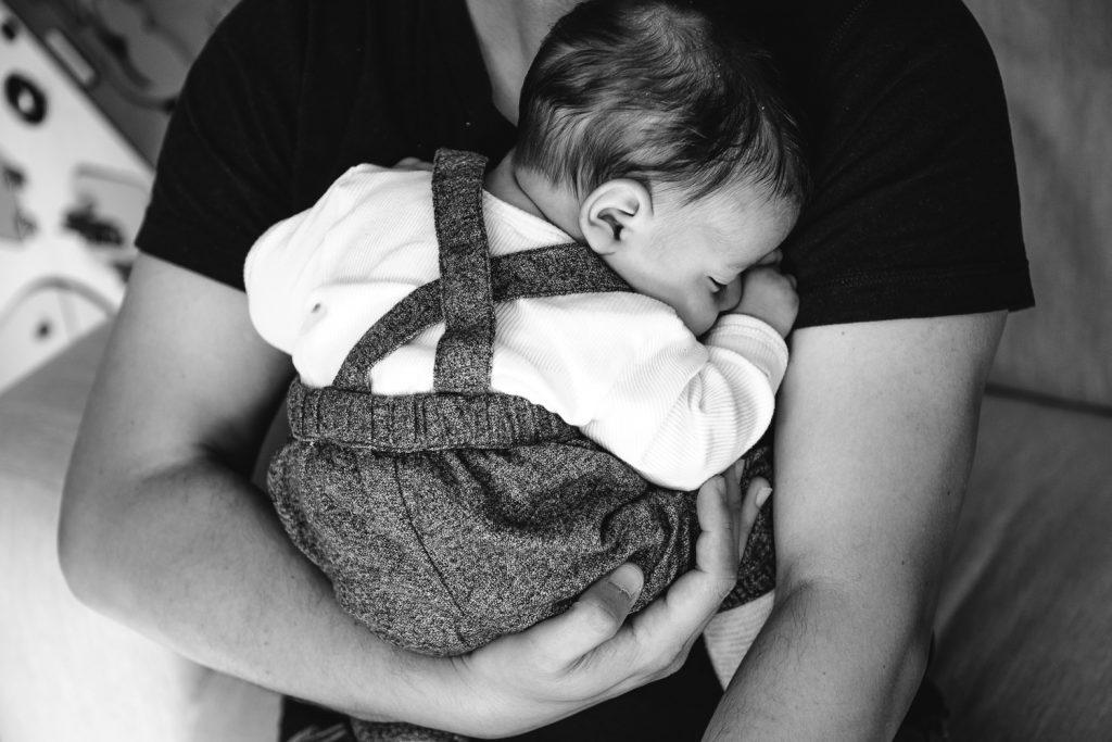 Nouveau-né qui dort en boule dans les bras de papa